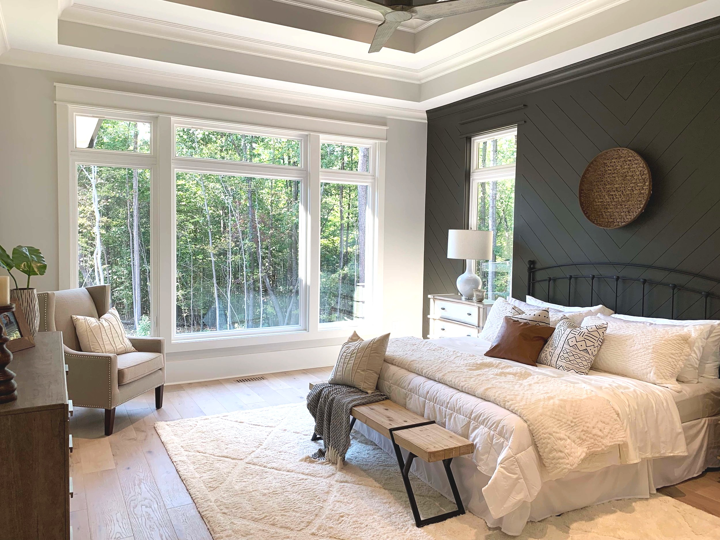 Master bedroom with large windows and accent wall.  Dark paint color.