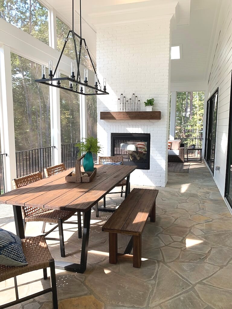 Screened porch with stone floor, dining table and chairs, double sided fireplace, chandelier and edison bulbs.