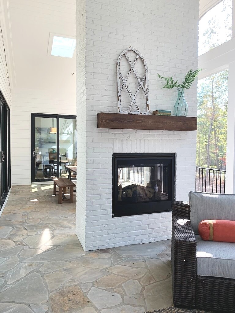 Screened in porch with stone floor, double sided fireplace, white painted brick and shiplap ceiling.