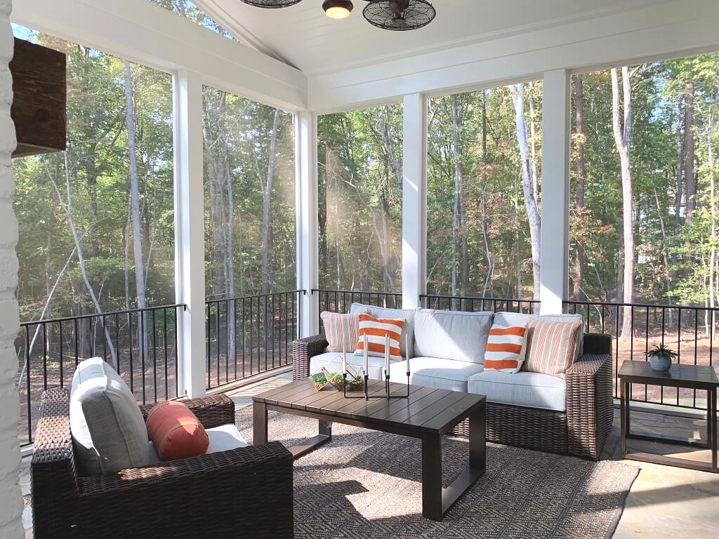 Screened in porch furniture and iron railing.