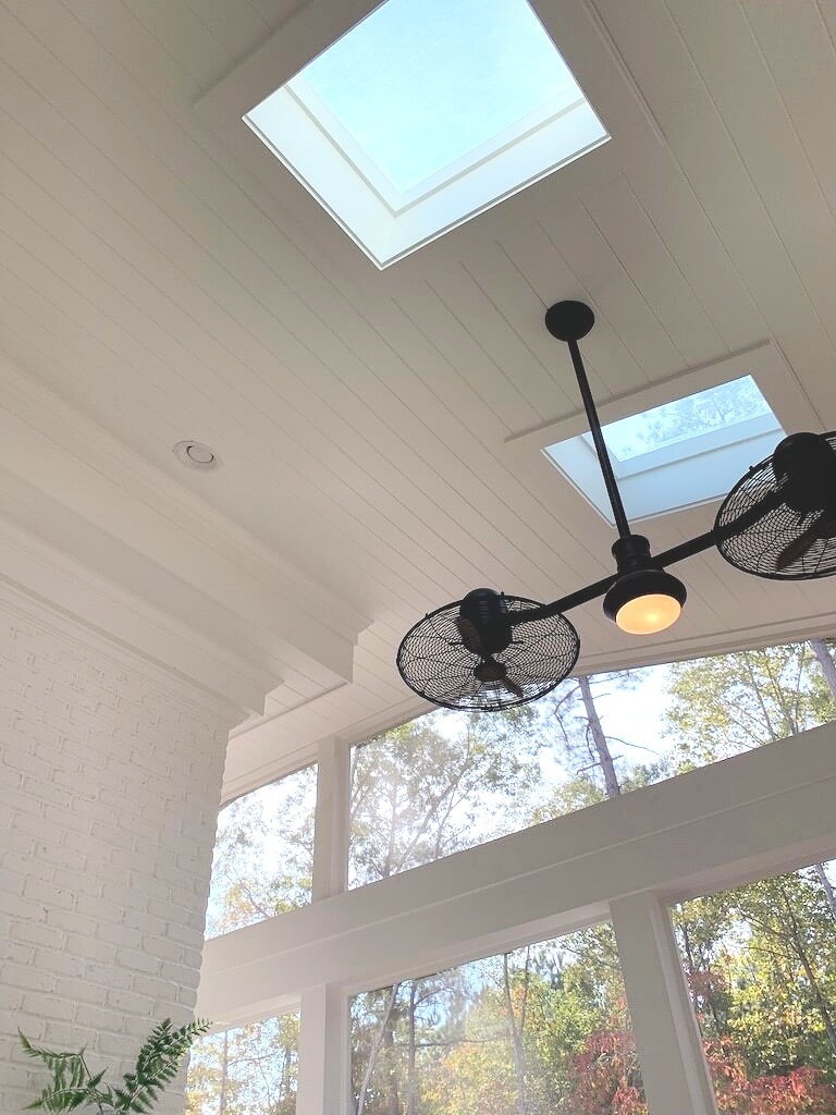 Farmhouse style screened in porch featuring white painted brick, shiplap ceiling and fun double ceiling fan.
