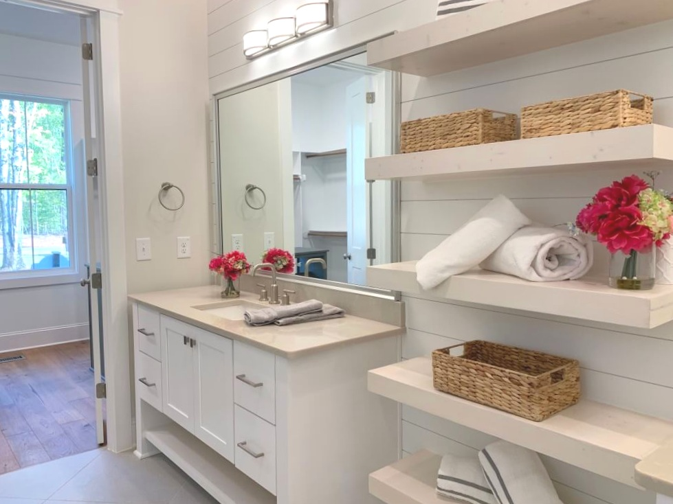 Bathroom with white cabinets and open shelving.