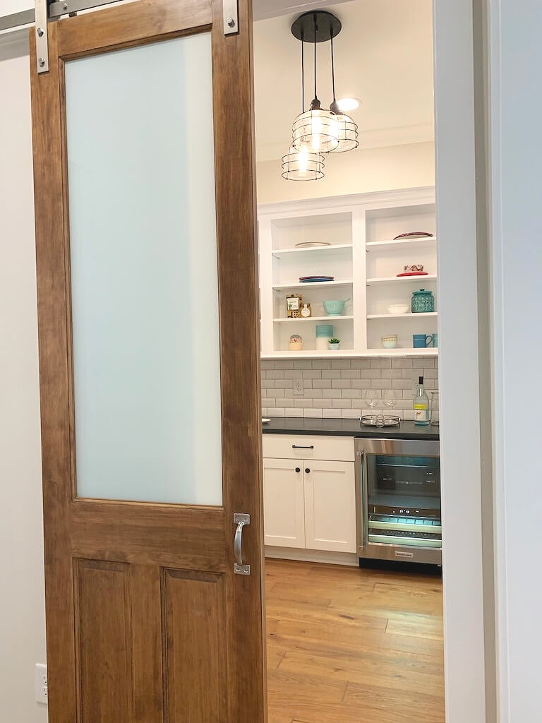 Farmhouse style kitchen butler's pantry with barn door, subway tile, wood floors and white cabinets.