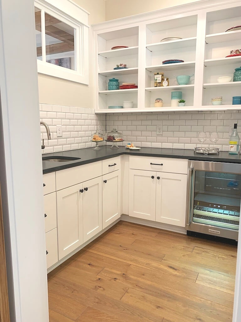 Kitchen butlers pantry with wide plank wood floors, white cabinets, black honed granite counter and open shelving.