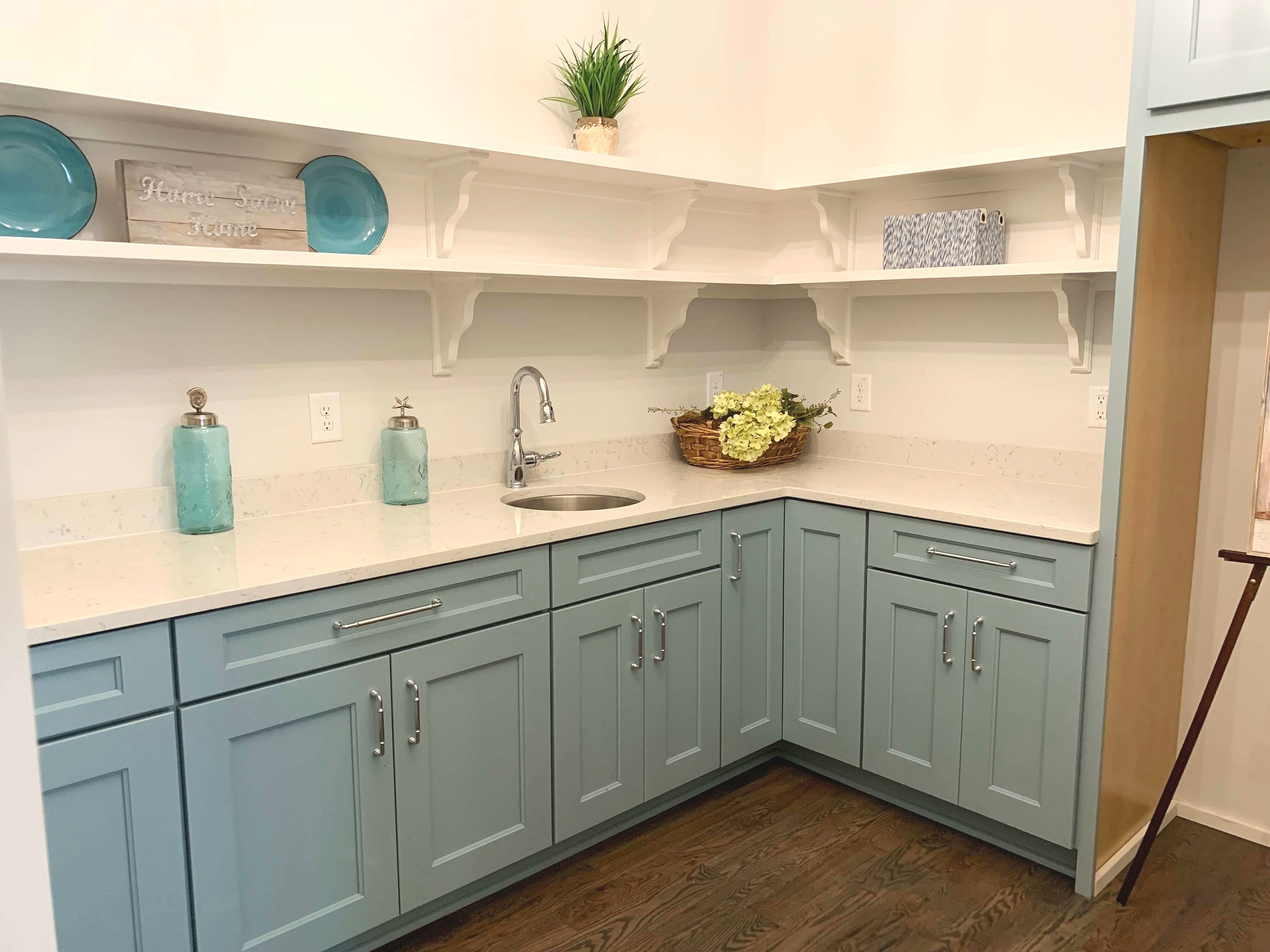 Kitchen butler's pantry with blue cabinets, open shelving, quartz counters and bar sink.