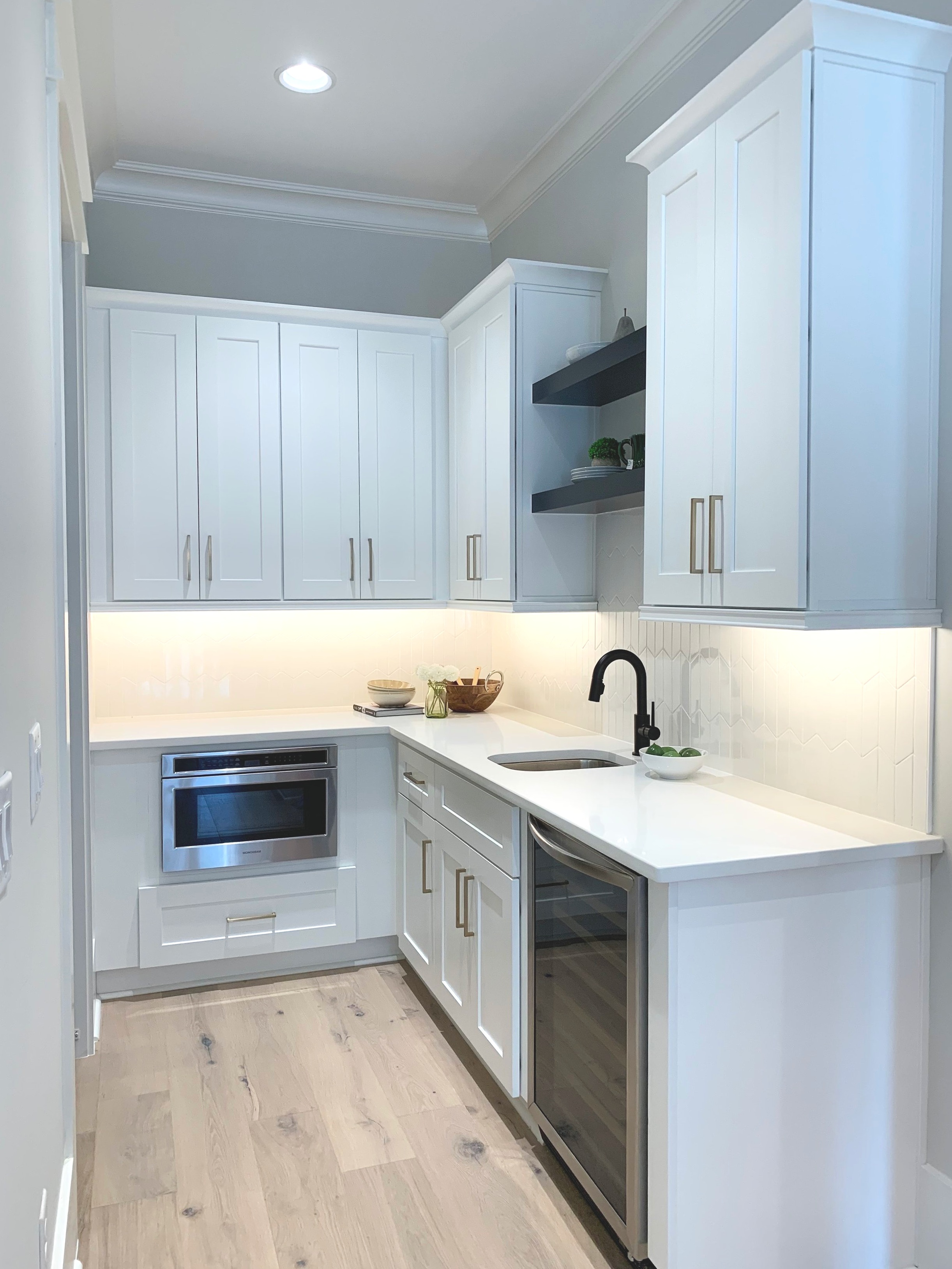 Butlers pantry with limed oak flooring, white cabinets, quartz counters and wine fridge.