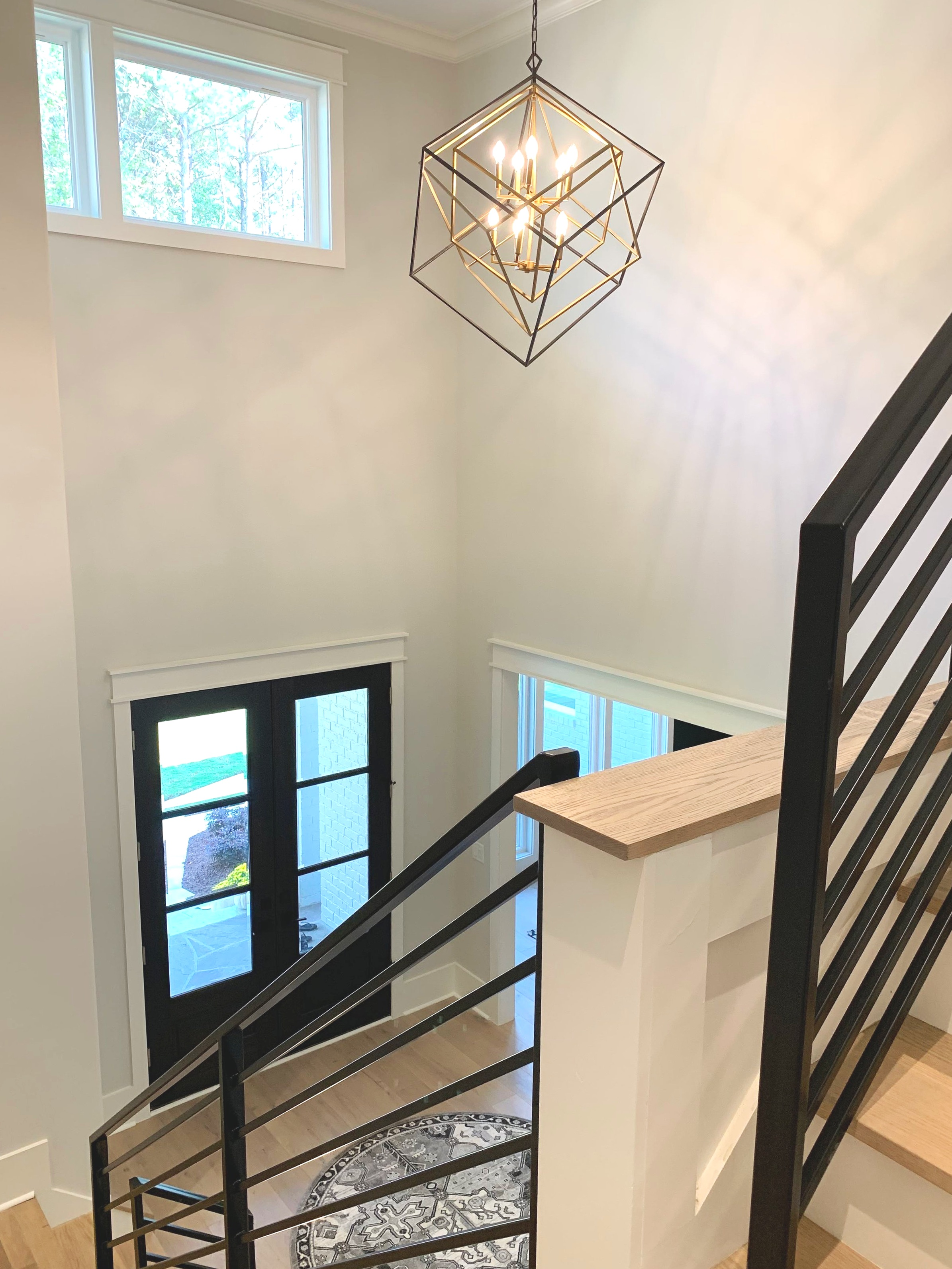 Modern, transitional, contemporary, updated traditional home with metal railings on staircase and contemporary lighting.