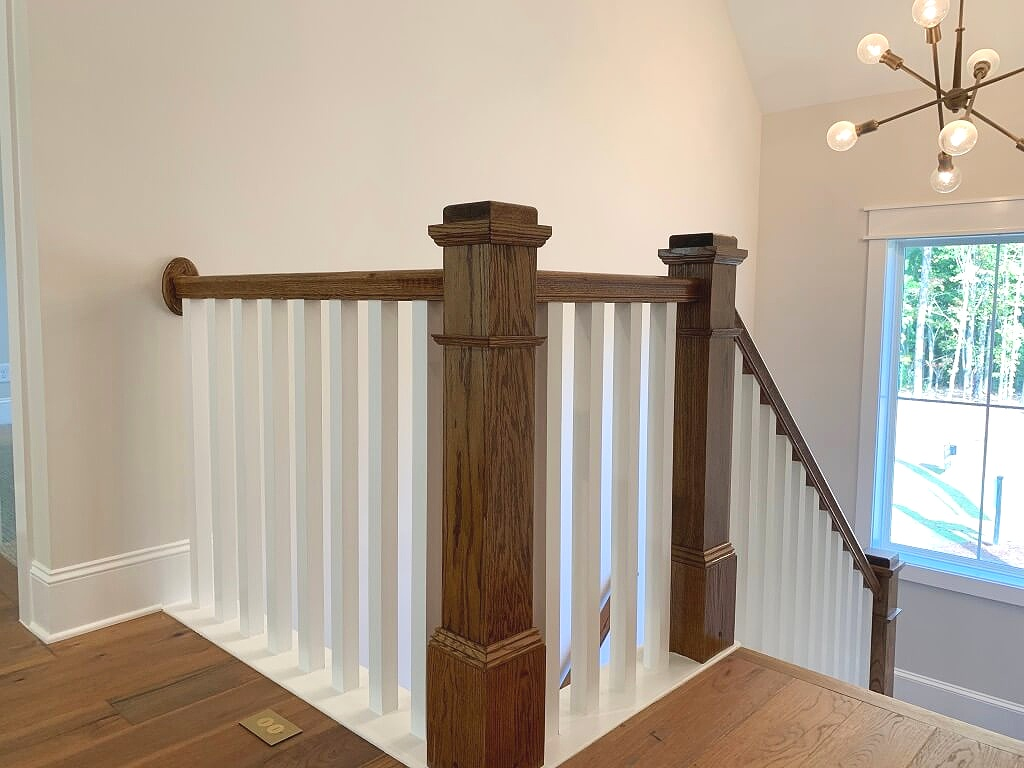 Farmhouse style traditional stairway with square painted spindles and mission style stained wood posts.
