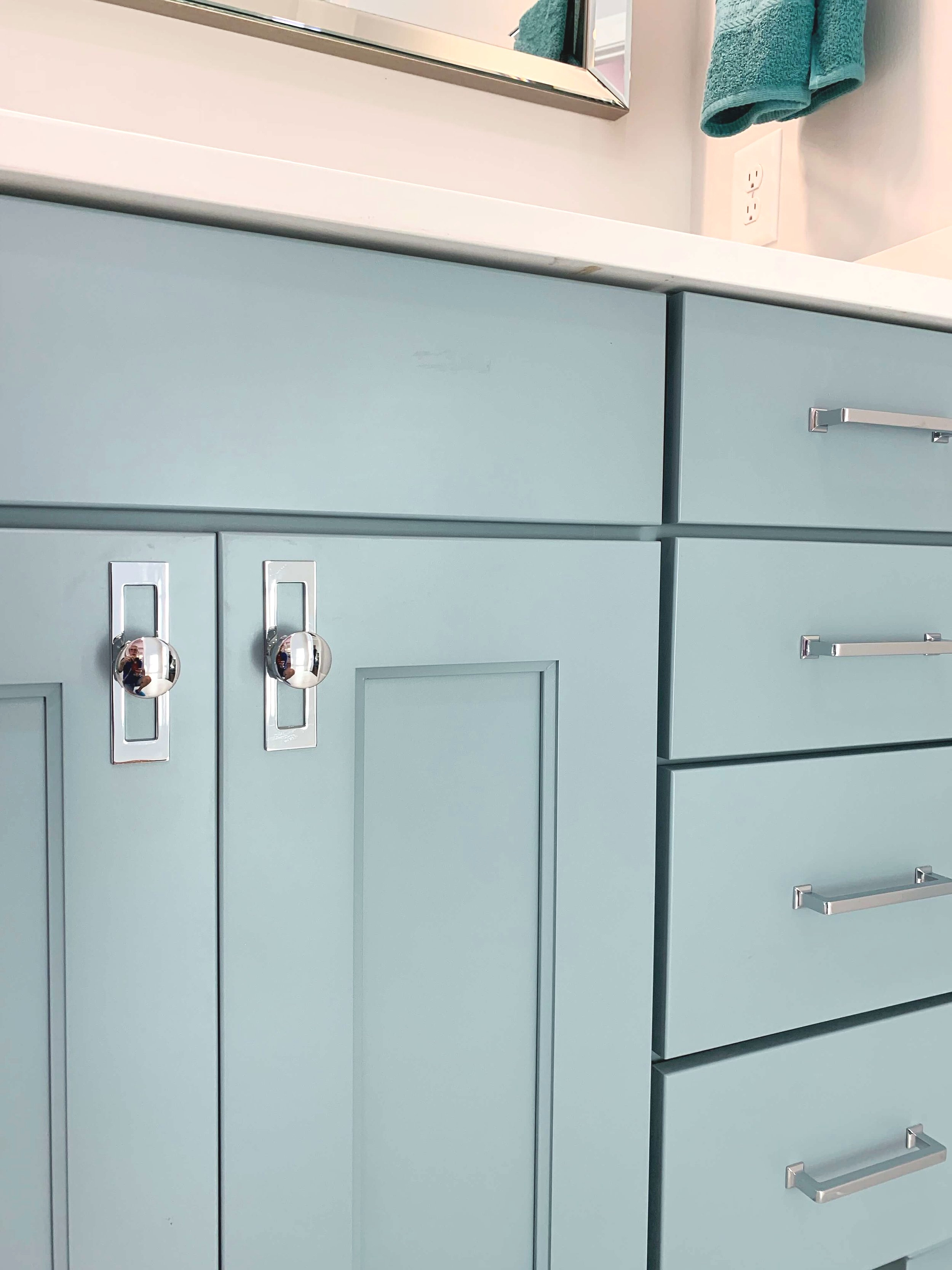 Blue bathroom cabinets with updated modern chrome hardware knobs and pulls.