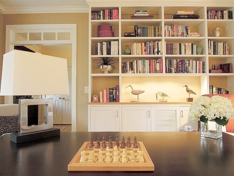 Custom shelving with LED accent lighting displays a collection of carved wood shore birds and keeps favorite books organized.