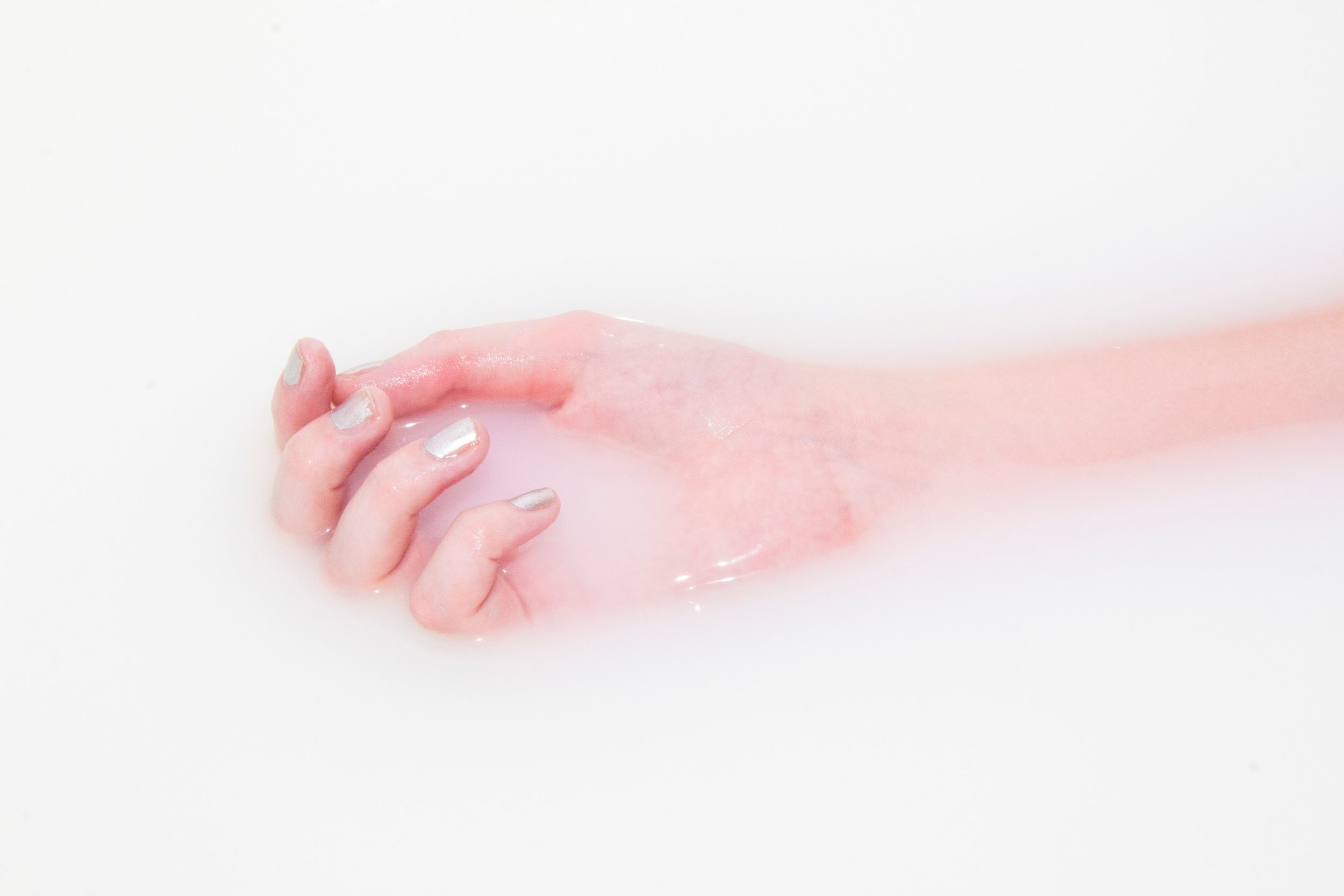A hand with light colored polish lays in a bath of milky water.