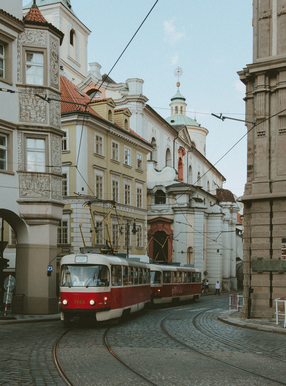 A red and white trolley rides through a cobblestone street in Prague. @Jeffrey Czum