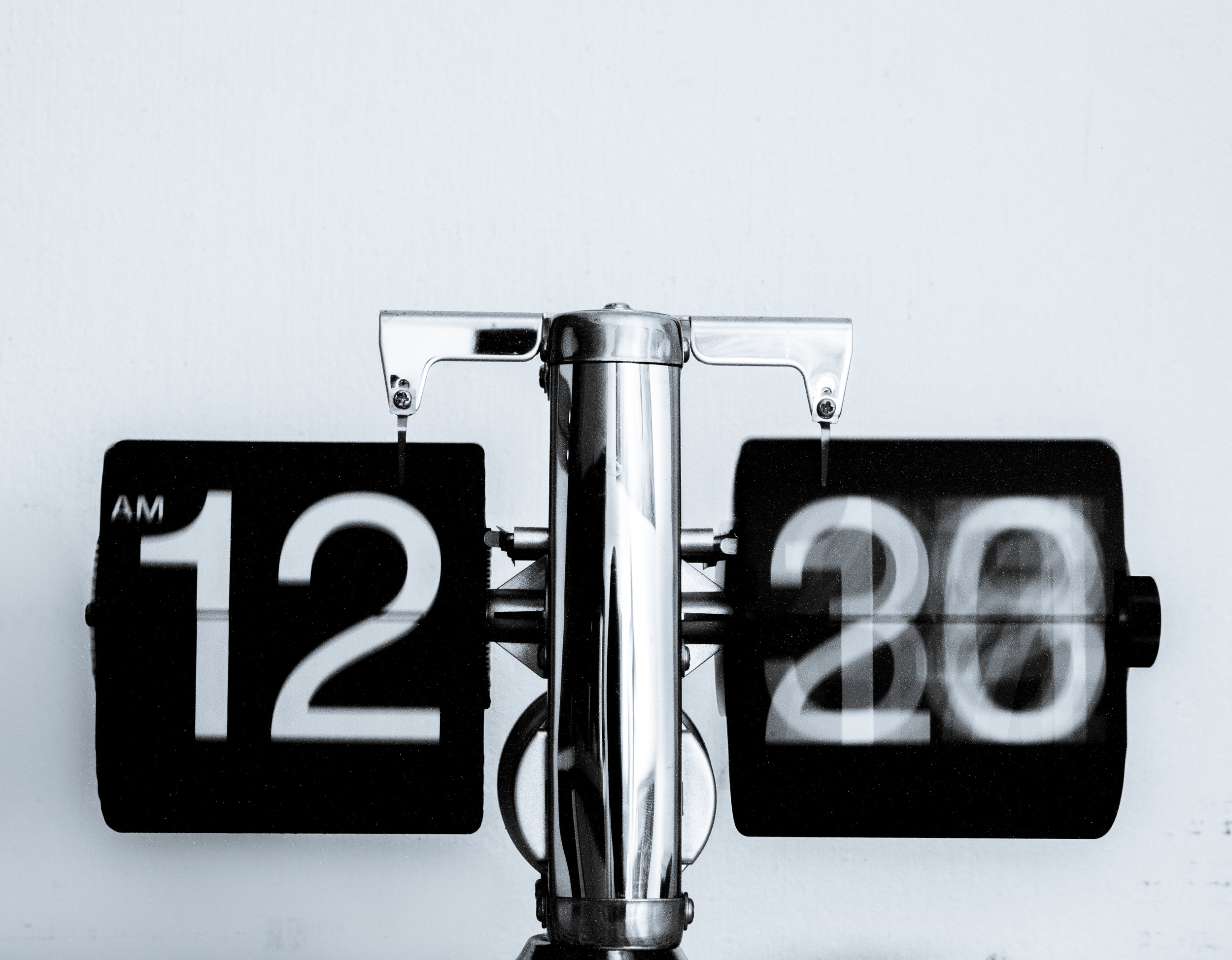 A clock with 12 am on one flip piece and a blurred number on the second.