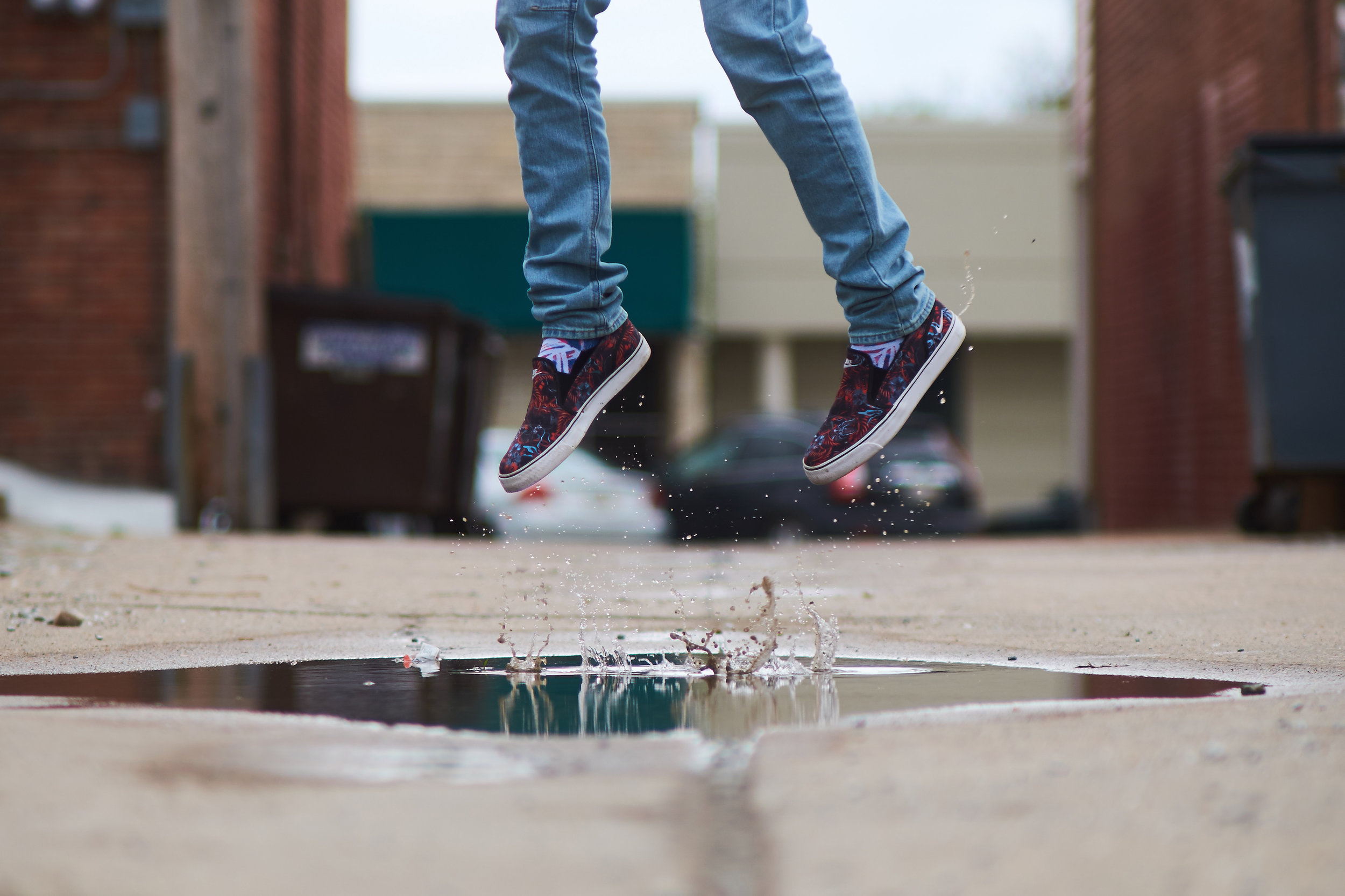 A person's legs in red shoes jump over a puddle in an alleyway.
