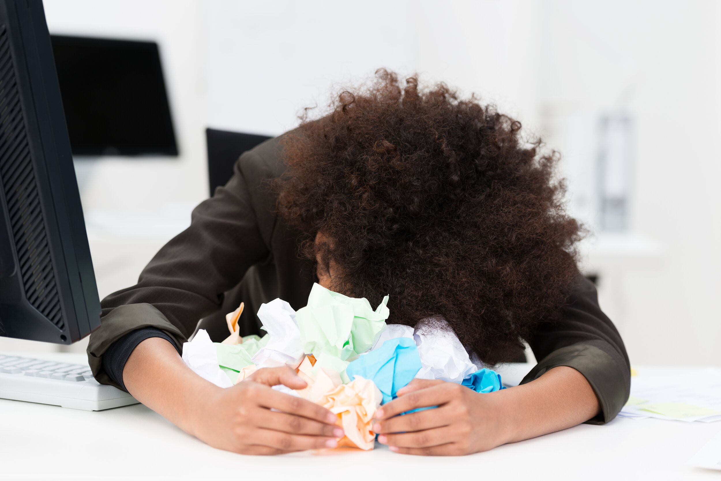 Distraught writer has her head resting on a pile of crumpled up paper.