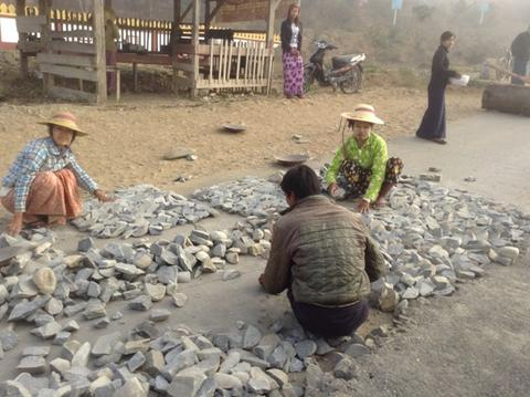 Road-making in Myanmar – Village women sorting rocks prior to the laying of the road