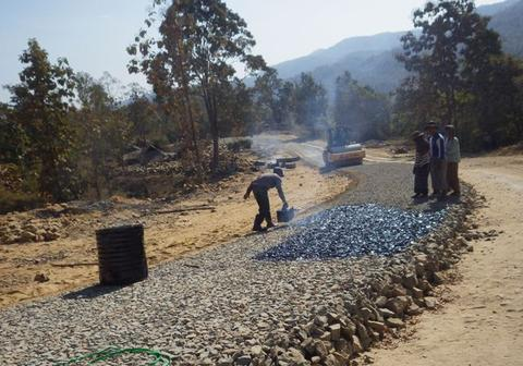 The bitumen being laid over the rocks from perforated kerosene tine, prior to rolling.