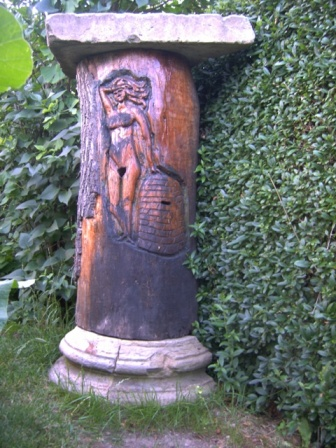 A Carved Klotzbeute – no longer containing bees, but used as a garden ornament. The lighter lid on top, which could be removed to inspect the hive, has been replaced by a heavier concrete lid.