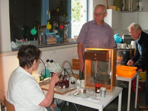 Frau Winkler at the microscope, Herr Winkler in the check shirt. CO2 bottles in the background. In the foreground is the glass-walled observation box to inspect the queens.