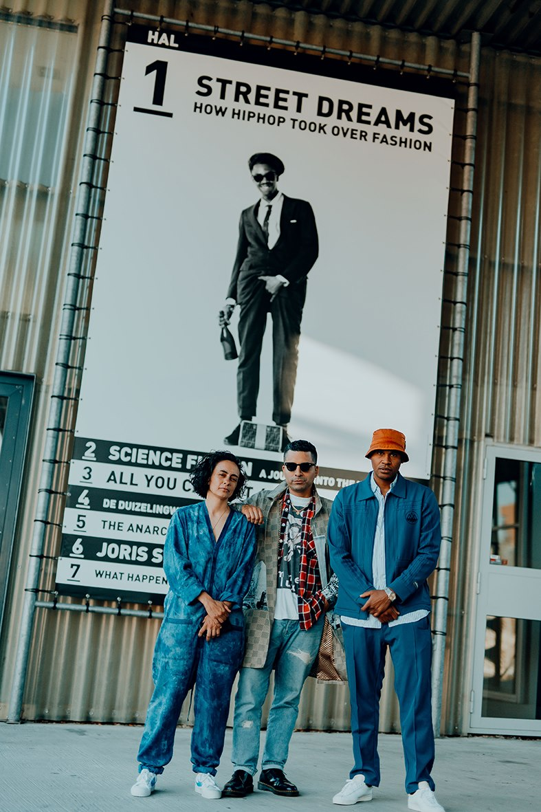 Image by Isabel Janssen -  Outsider.i  : Aruna Vermeulen, Angelo Baque and Lee Stuart at Kunsthal in front of exhibition poster