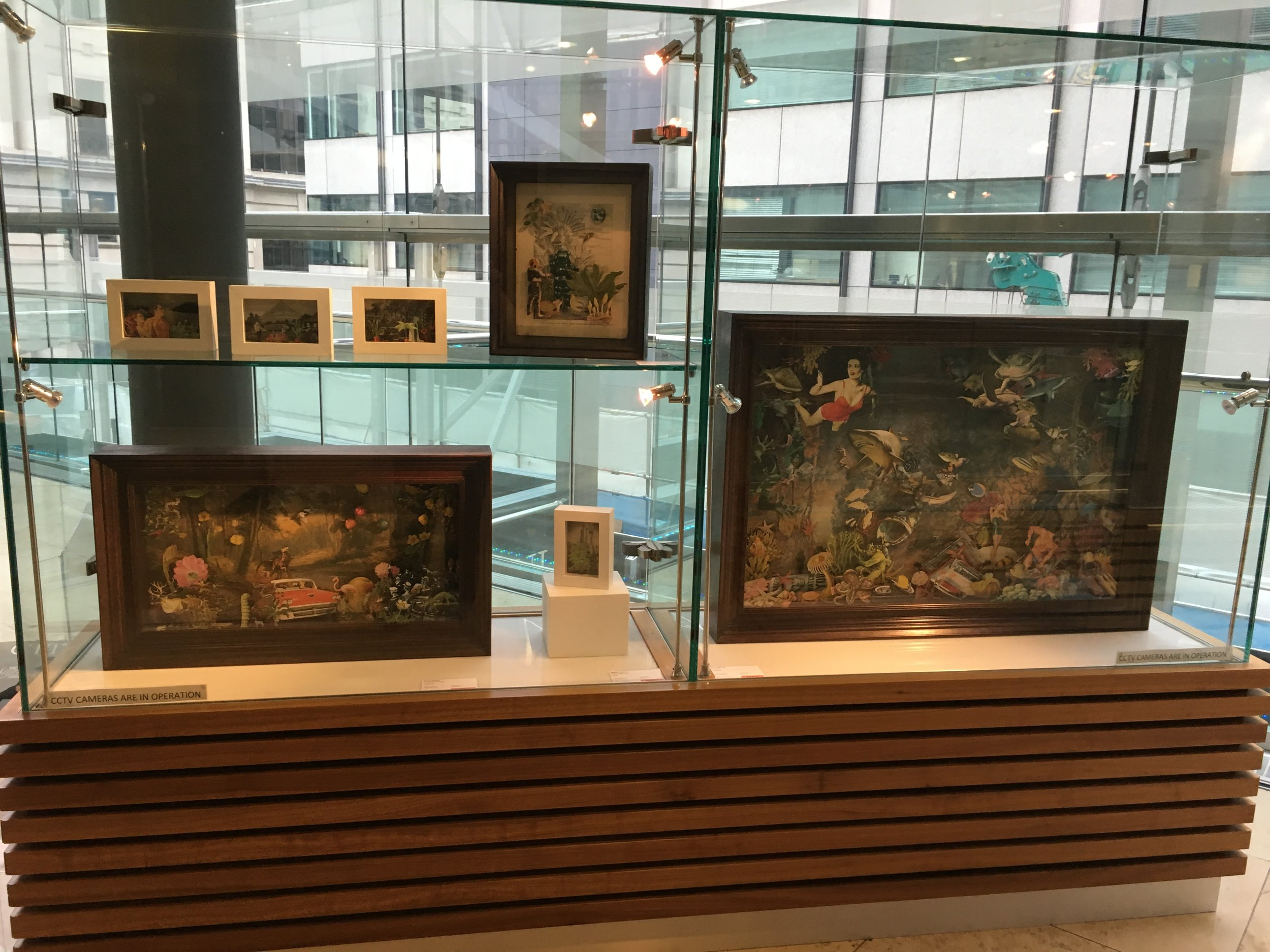Display case at the top of the escalators featuring Maria Rivans' original collages in bespoke 3D boxes.
