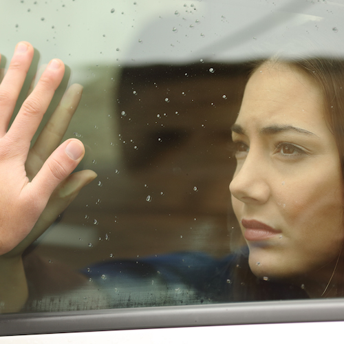 woman touches hands through glass in rain looking distressed