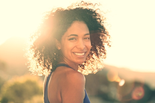 young woman smiles in the sun