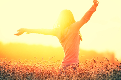 young woman dances in a corn field