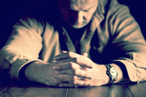 man looks down at table with hands folded
