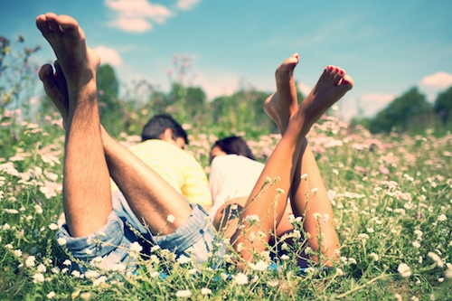 couple lay barefoot in field looking lovingly at eachother