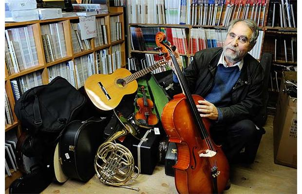 Janos Maté shows some of the donated instruments at Tapestry Music that will be sent to Paraguay's Recycled Orchestra.   Photograph by   Dan Toulgoet, Vancouver Courier