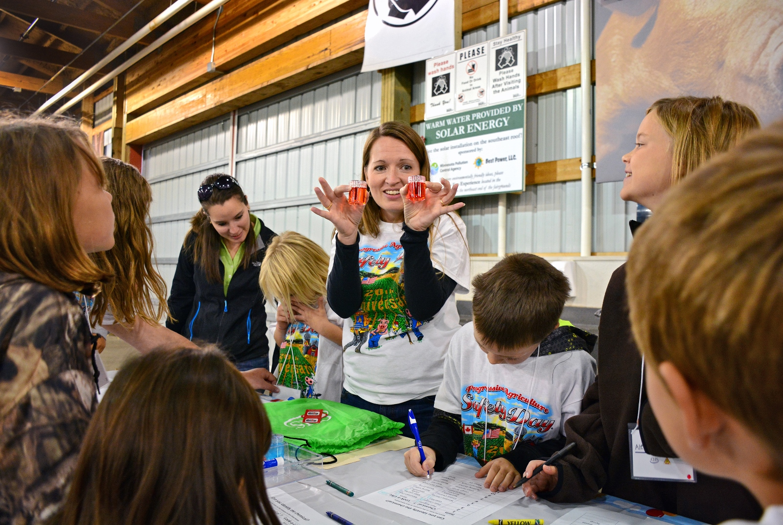 Young attendees at a Progressive Agriculture Attendee Day attempt to identify which substance is a sweet beverage and which is a hazardous chemical. The exercise teaches children not to make assumptions about liquids they find at home or on a farm.
