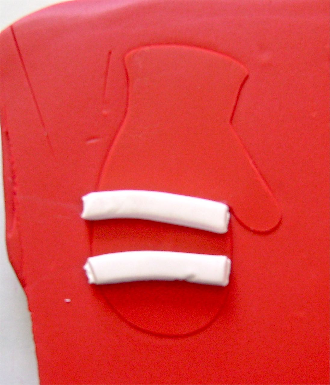 step 2 - Roll out two small pieces for stripes on the mittens.  Cut them to equal sizes and position them on the clay.