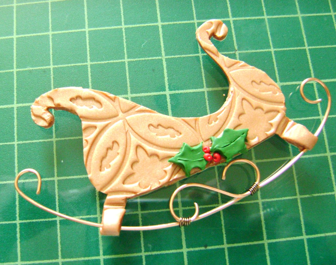 step 10 - Place the runner on the legs of the sleigh. Press lightly into the clay. Cover with the extra leg pieces and press together.