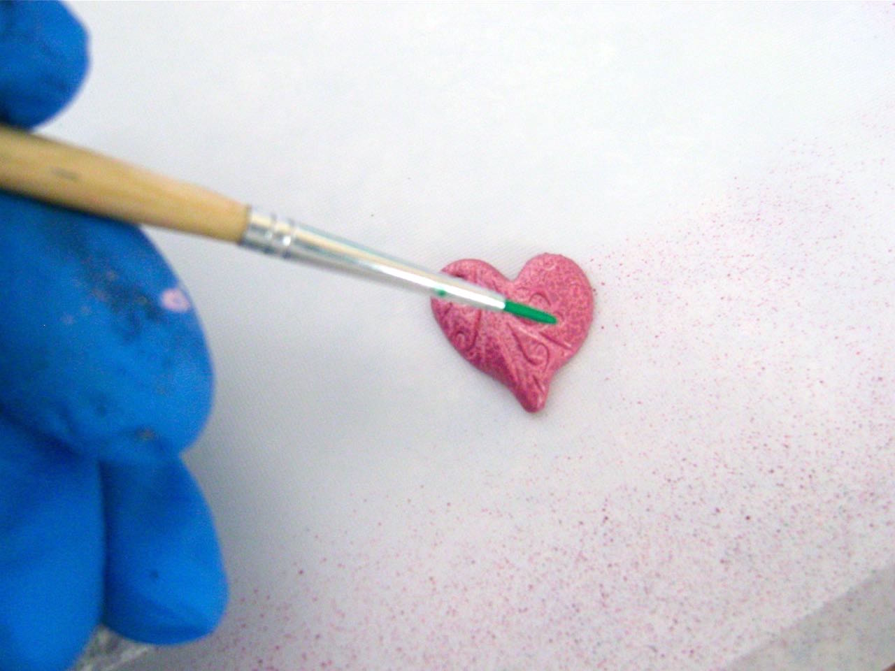 step 11 - Create contrasts to bring out the small details in the surface of the pink and mauve hearts.  In a small container, water down a little of the green color.  Use a small brush to apply it across the hearts being sure it seeps into the impressions.  Immediately dab at the paint with a rag to remove most of the wet paint leaving color in the impressions.
