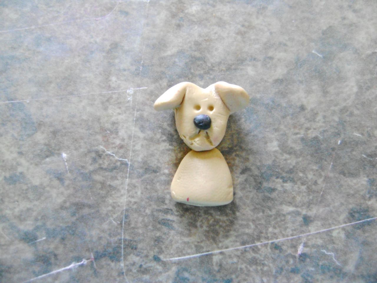 step 9 - Roll a glob of clay to create a small half body and press the head onto it.