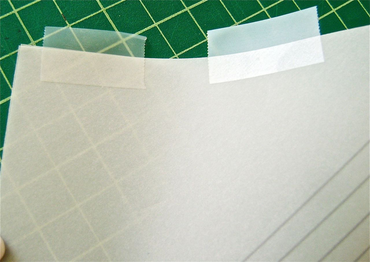 step 4 - Match the back edges and placetransparent tape along the length. Fold the tape over to adhere to the other edge. Set aside.
