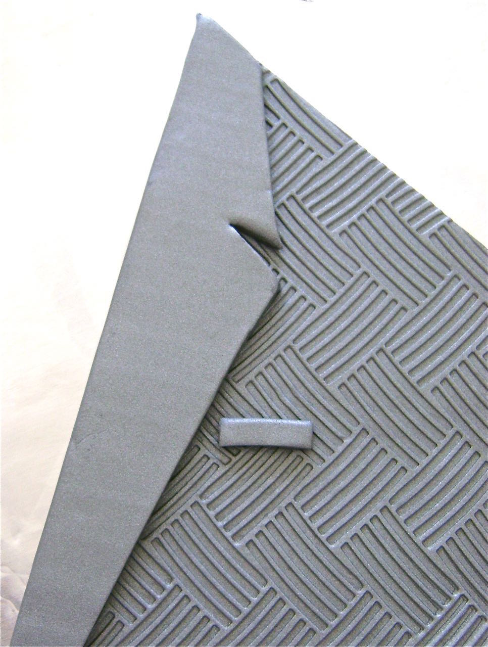 step 12 - Cut the card stock lapel away from the sconce template. Use it as a guide to cut out two clay lapels. Do not arrange the lapels on the sconce yet. Cut a half inch long thin piece of clay for the breast pocket and press it in place.