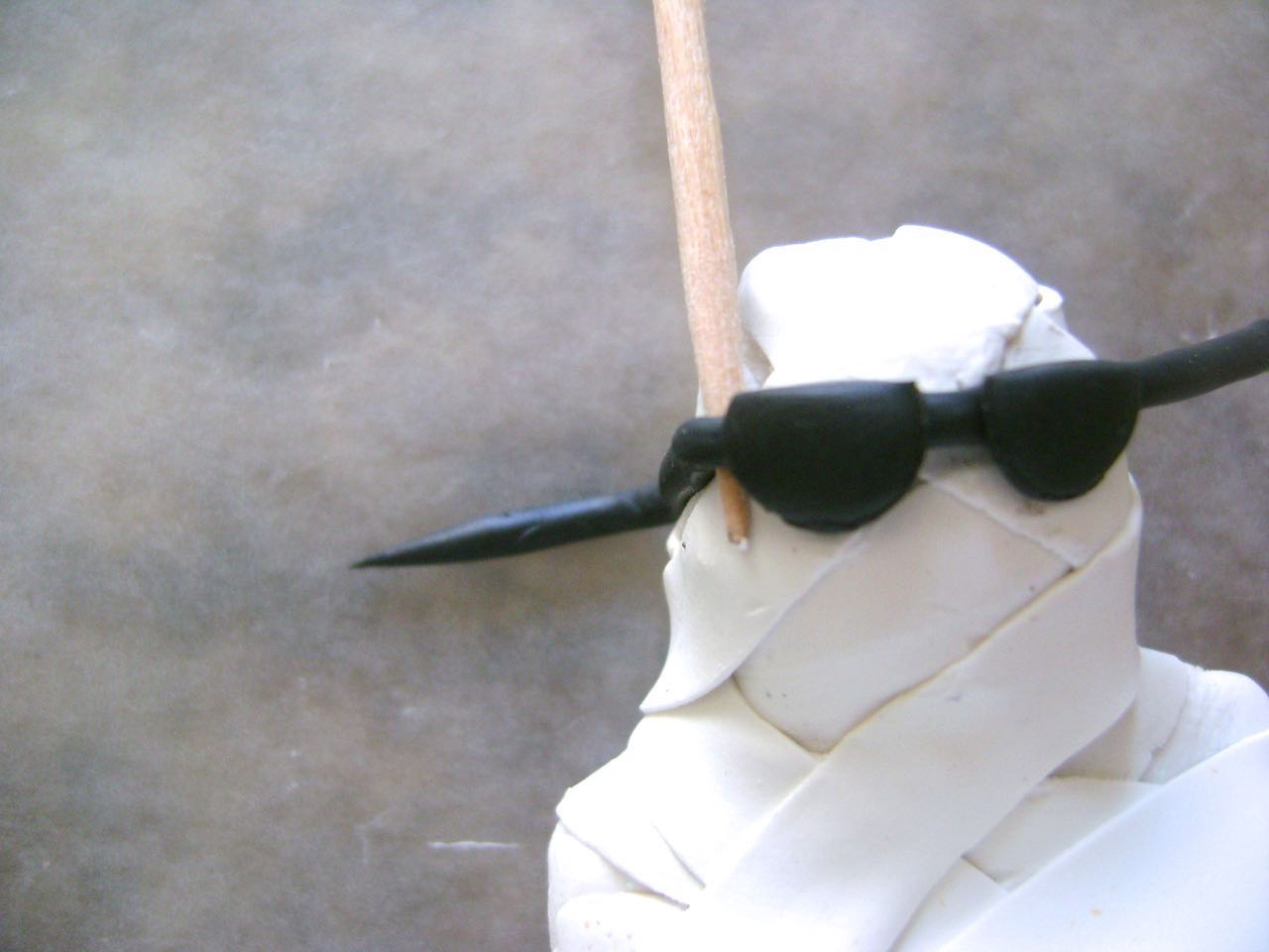 step 8 - Position the glasses on the mummy.  Place a toothpick against the corner of the glasses and wrap the arm back to the ear area.  Cut away excess black clay and press the arm to stick it to the head.