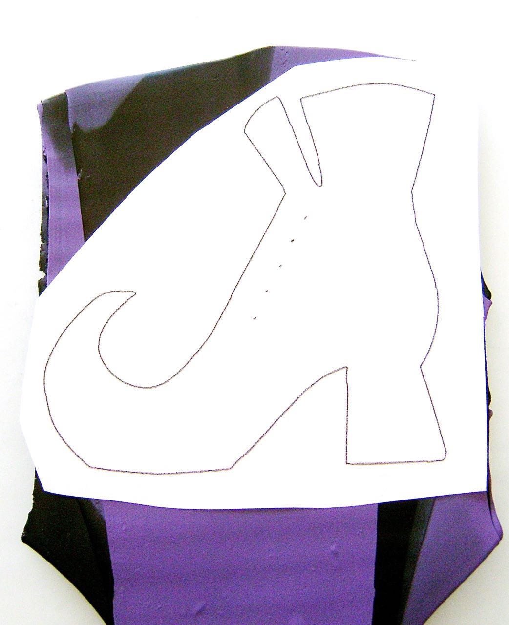 step 2 - When you're happy with the color mix, lay the clay on a piece of wax paper.  Set the stencil on top and cut through the paper tracing the boot shape with a sharp craft knife.  Mark dots for the lace holes.