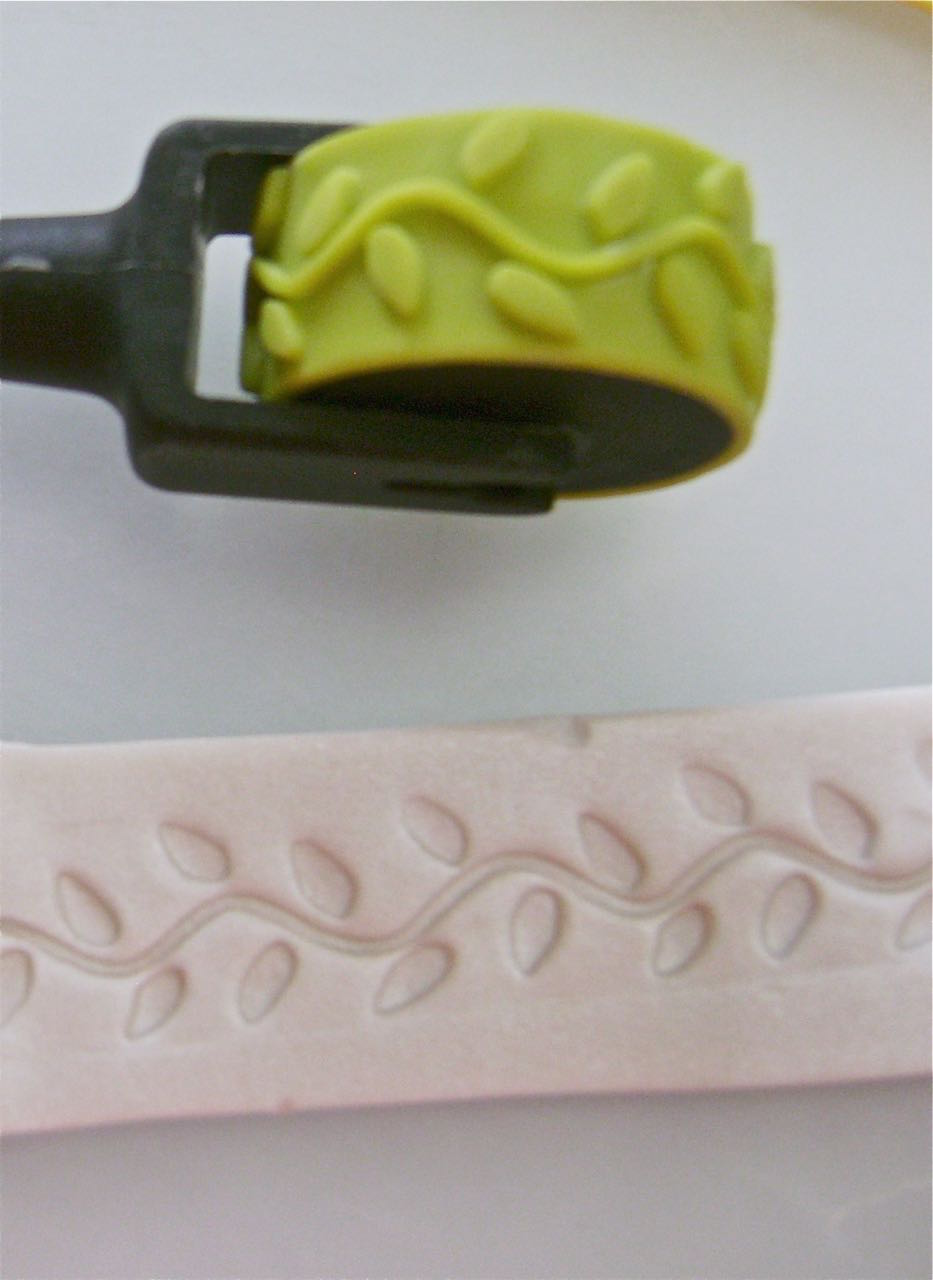 "step 3 - Cut .50"" Inch strips from Pearl clay and join them, blending the edges until you have a long enough strip to spiral around your mirror handle from top to bottom.  Before you wrap the handle, roll across the long strip with the vine design texture wheel."