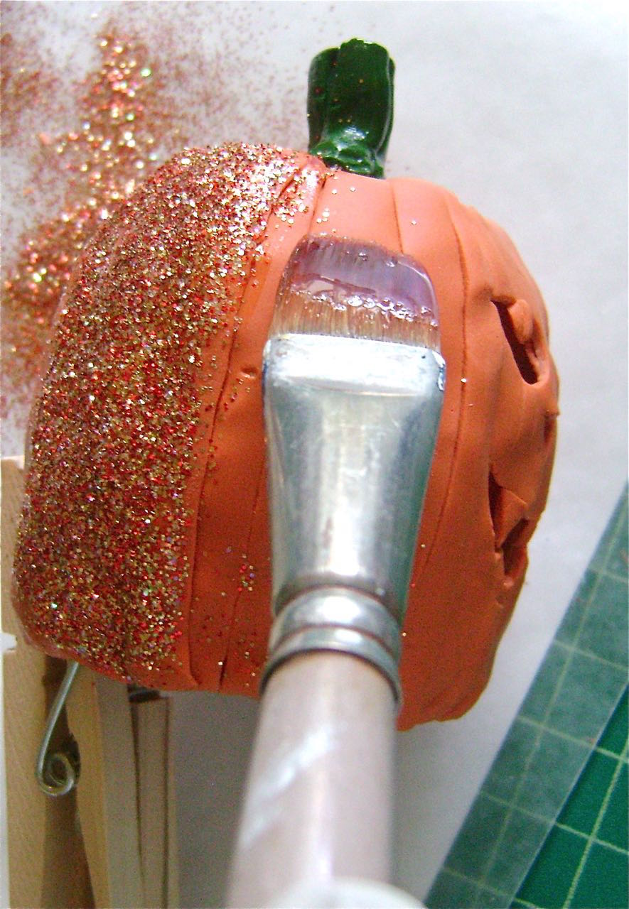 step 13 - Brush glaze on the pumpkin and sprinkle with orange glitter.  Shake off excess.  Work in sections.  A clothespin is a convenient way to handle the clay during this step.  When the glaze is dry and no more glitter can be shaken off, use the brush to paint over the glitter to keep it from shedding.
