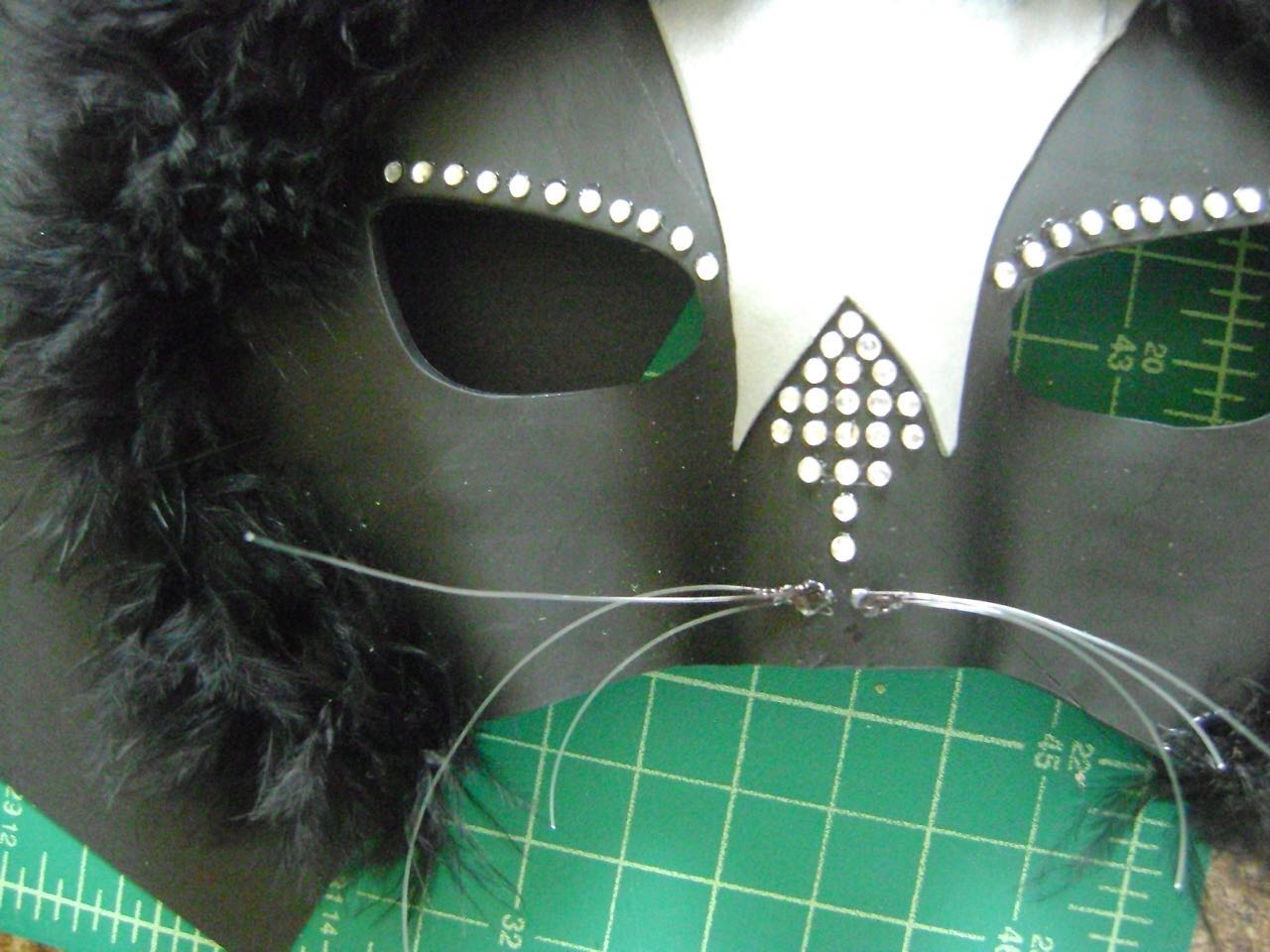 step 13 - Cut six, three-inch pieces of clear fishing line or beading thread. Join three at one end with hot glue then hot glue the joined ends below the bottom rhinestone. Repeat with the other three pieces. Trim the whiskers to the desired length. Hot glue the large rhinestone over the whiskers.
