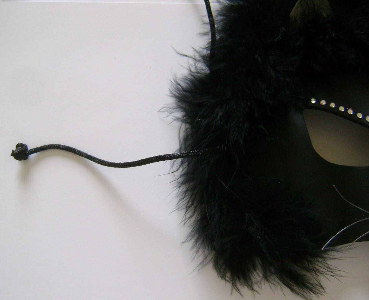 """step 14 - Bring 13"""" cord pieces from the back of the mask to the front. Tie a double knot in each and cut off the excess. Pull the cord to the back to hide the knot in the fur."""