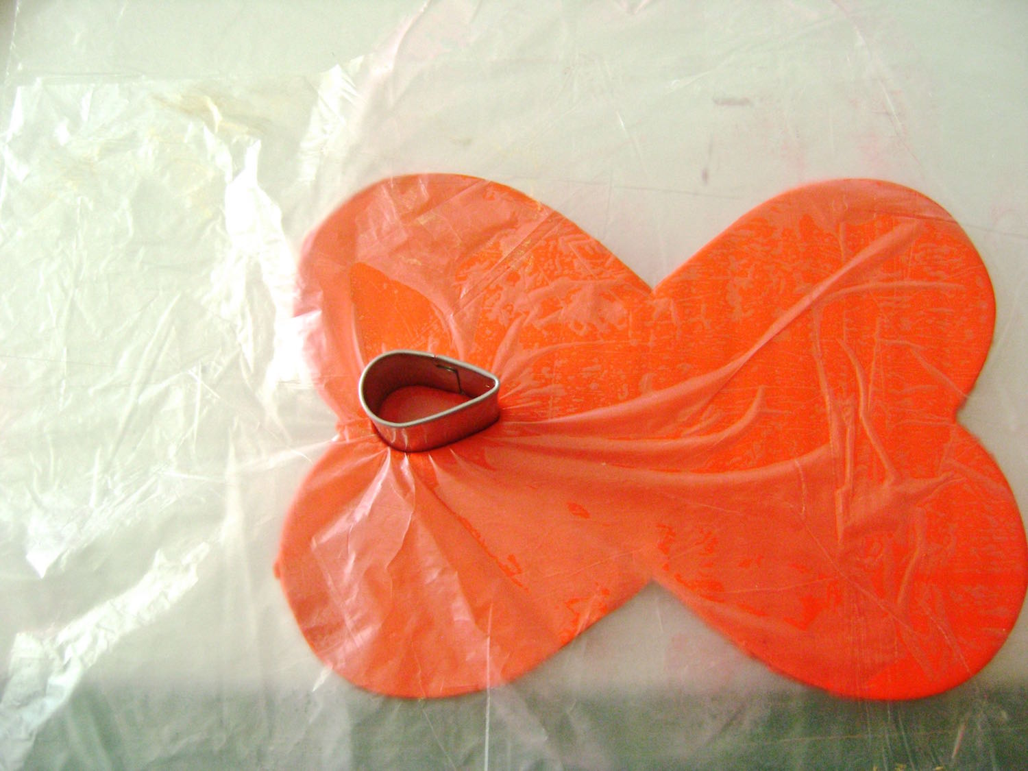 step 3 - Cover the cuff with plastic wrap. With a teardrop shaped cutter, press down to cut a hole in the clay on the left side of the cuff. Position the cutter on the right side and create an identical cut.