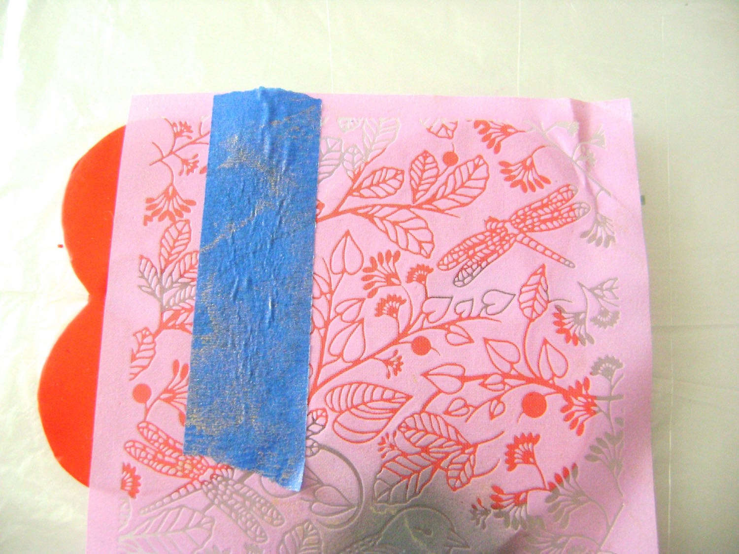 step 4 - Lay the silkscreen shiny side down over the clay. Place tape on the silkscreen to mark the center of the cuff.