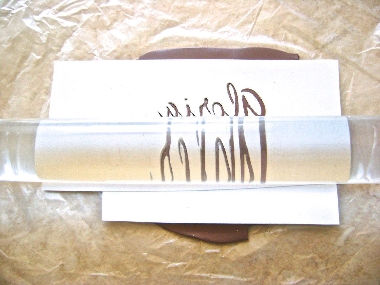 step 4 - Place the card stock onto the clay with the unreadable side facing up.  Either run them together through the conditioning machine on the widest setting, or roll over the signature with an acrylic roller until the clay has risen up to the top layer of the card stock.  Carefully peel the card stock away from the clay.
