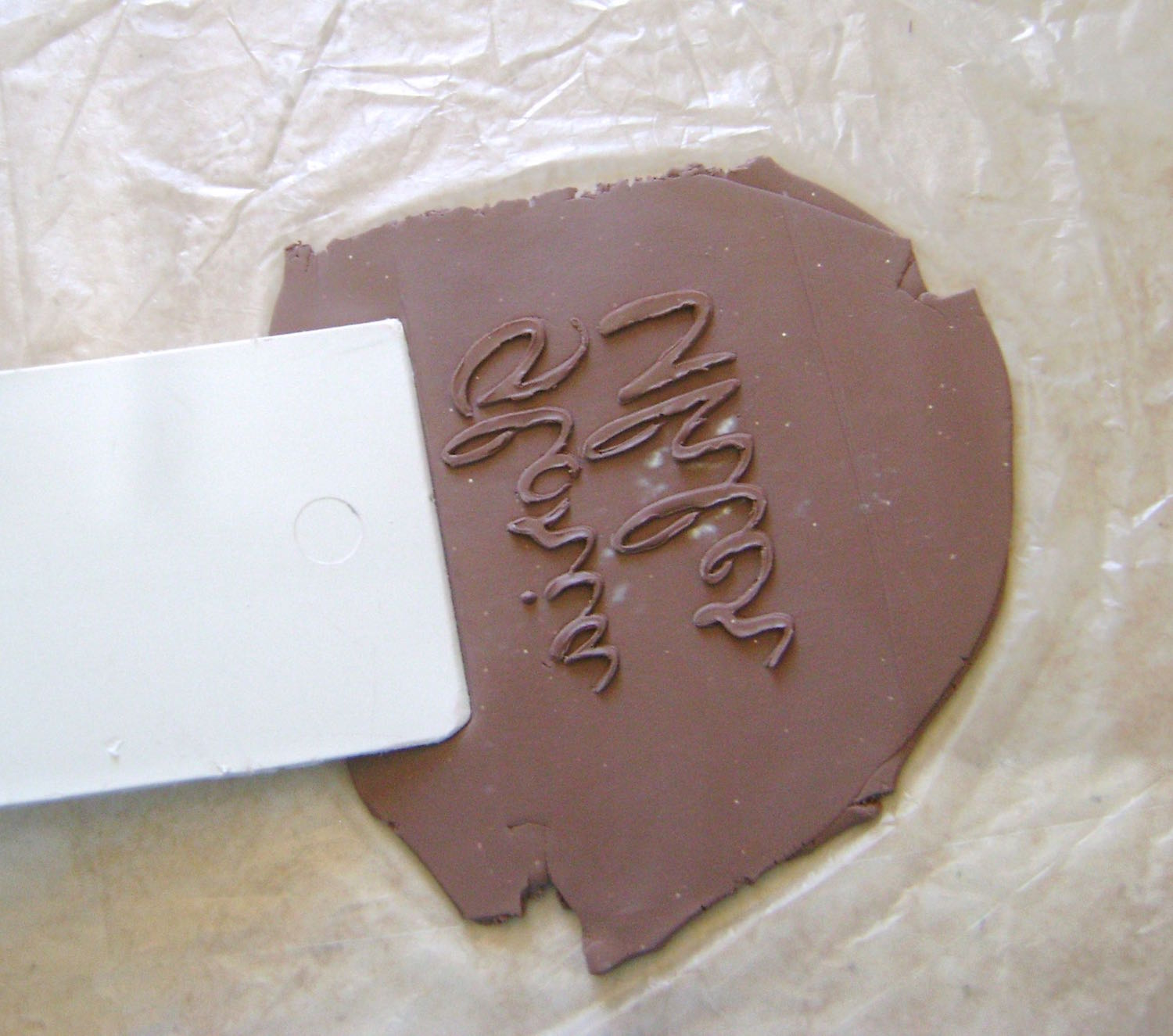 step 5 - Press a plastic spatula outside the signature area to flatten the surrounding clay slightly.