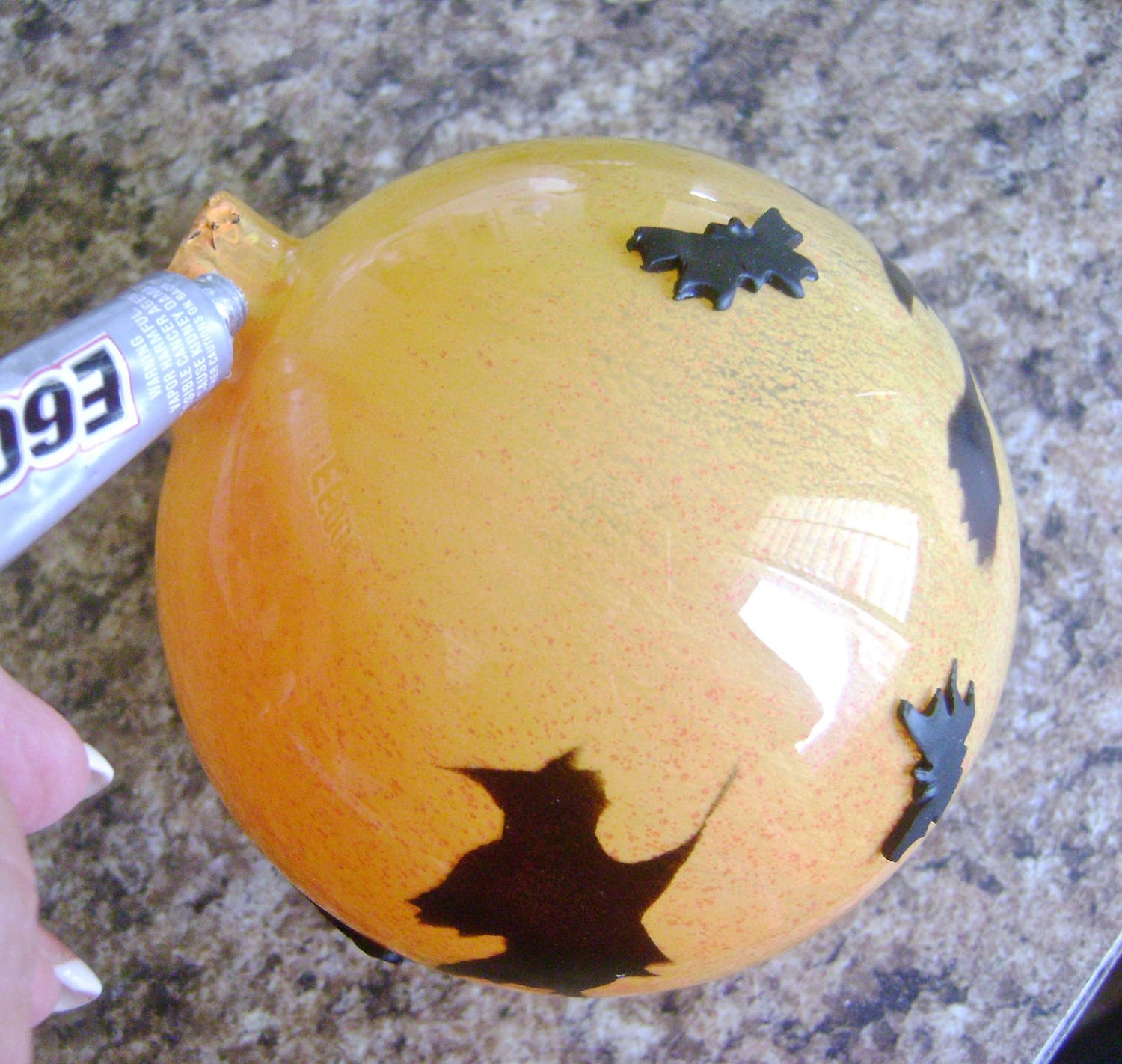 step 15 - After the yellow paint has dried, apply E6000 to the neck opening of the ornament. Press the hat onto the opening.