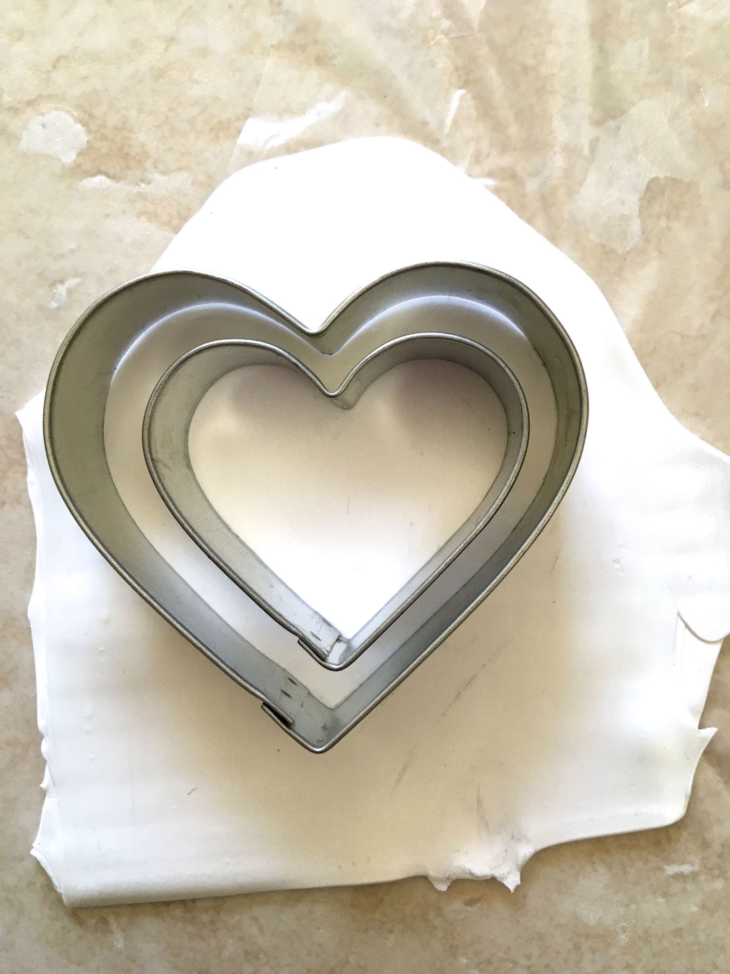 step 1 - Roll white clay on the # 2 setting. Cut a heart shape from the clay with a cutter larger than the one you will use for you final piece.